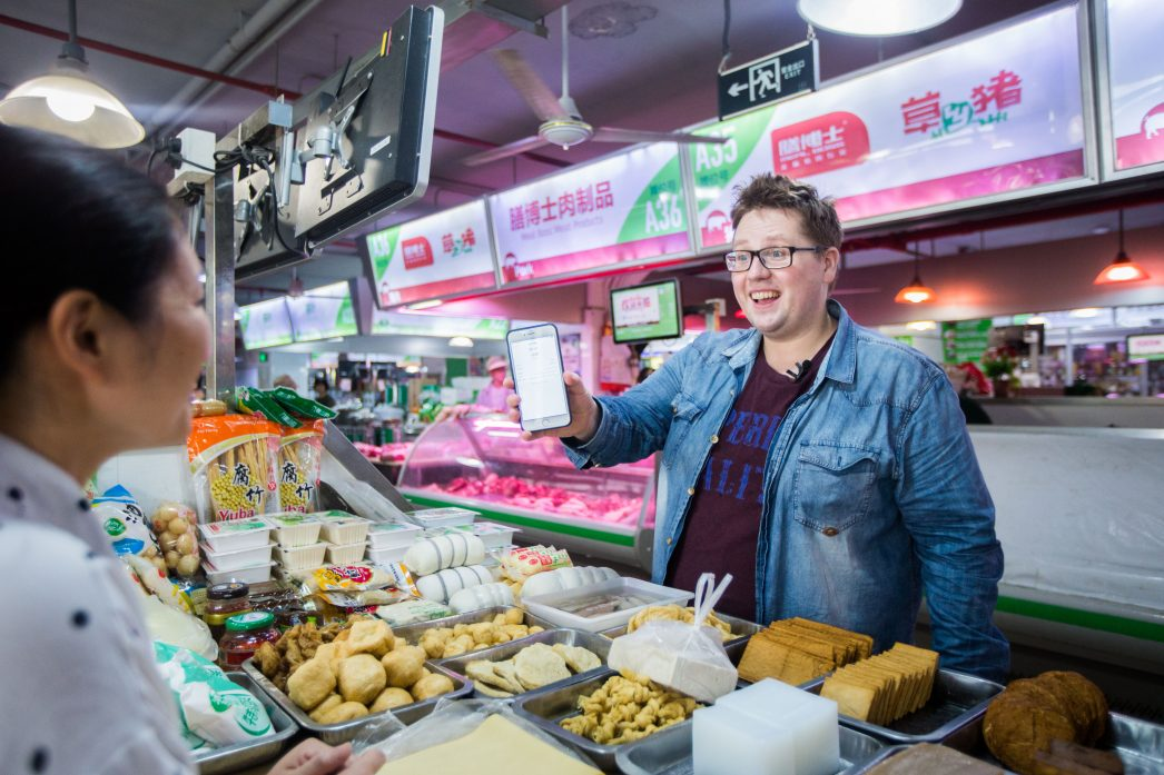 """Thomas Derksen est un jeune allemand de 28 ans vivant en Chine qui expose sa vie quotidienne à des millions de """"followers"""" comme ici dans un marché de Shanghai le 22 juin 2017."""
