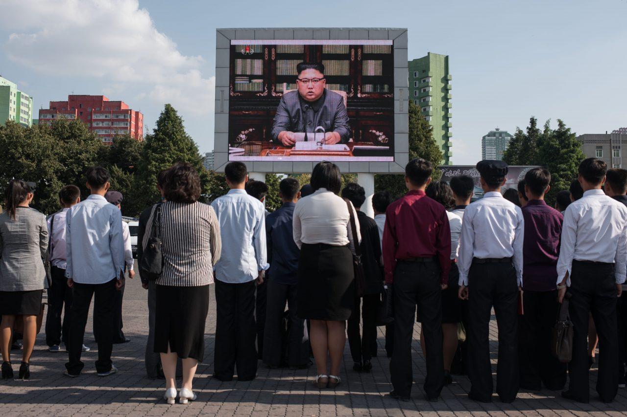 """Des Nord-coréens assistant à la déclaration de leur dirigeant Kim Jong-Un, retransmise sur grand écran à la gare centrale de Pyongyang, le 22 septembre 2017. Le président américain Donald Trump est """"mentalement dérangé"""" et """"paiera"""" pour ses menaces, a alors affirmé Kim Jong-Un, alors que le ministre nord-coréen des Affaires étrangères a laissé entendre que la Corée du Nord pour faire exploser une bombe à hydrogène dans l'océan Pacifique. (Crédits : Ed JONES / AFP)"""