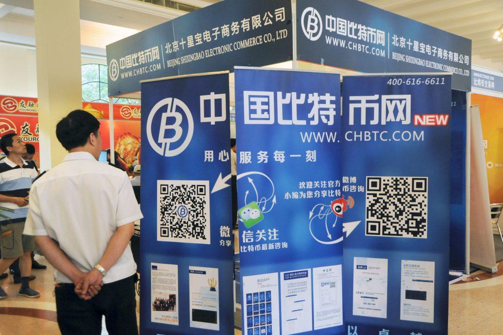 Un visiteur chinois s'arrête au stand de Chbtc.com, l'une des plateformes chinoises d'échange de bitcoins lors d'une salon à Shanghai, en Chine, le 28 juin 2014. (Crédits : Zhu lan / Imaginechina / via AFP)