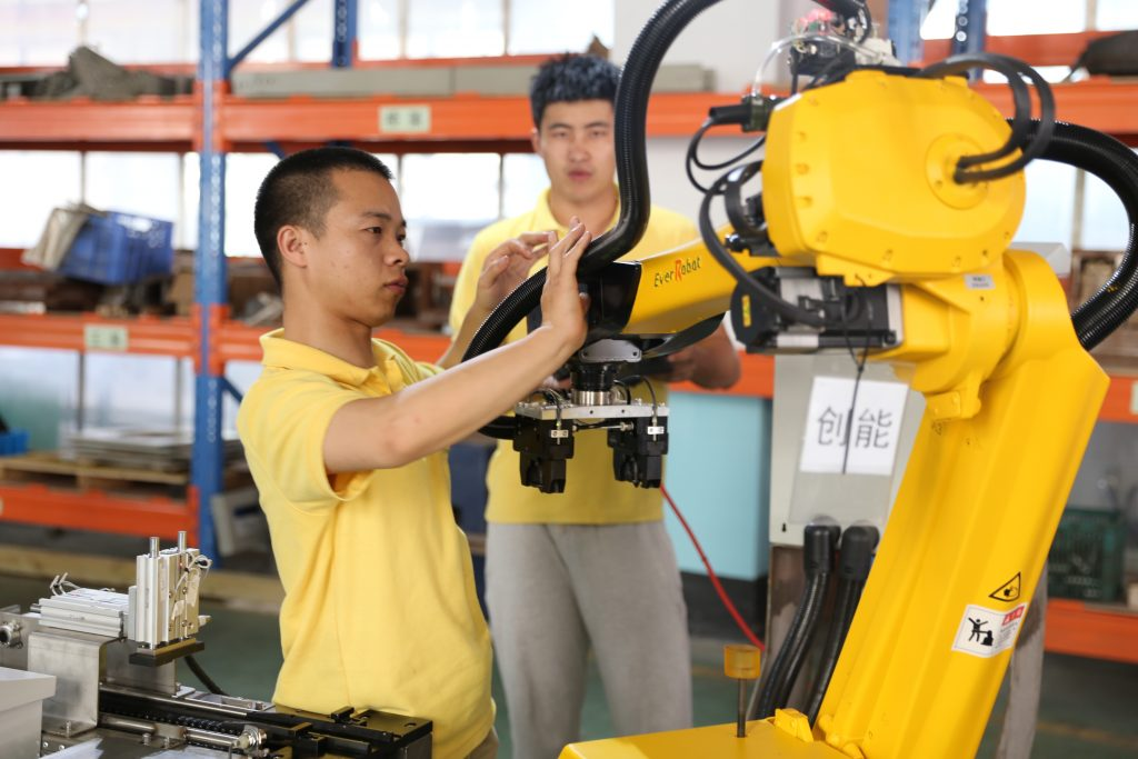-Un ouvrier chinois teste un bras robotique dans l'usine de Zhejiang EverRobot Robotics à Jiaxing, dans la province côtière du Zhejiang, au sud de Shanghai, le 25 août 2015. (Crédits : Wei wei / Imaginechina / via AFP)