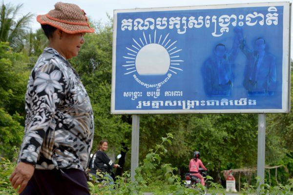 Cette photo prise le 5 août 2017 montre une femme marchant devant une affiche du Parti du sauvetage national du Cambodge (CNRP) avec les figures effacées de l'actuel leader du parti Kem Sokha et de l'ancien dirigeant Sam Rainsy, dans un village de la province de Pursat. L'opposition a été obligée de gommer l'image de son dirigeant en exil, Sam Rainsy, sur des milliers de panneaux et d'affiches à travers le pays. (Crédits : TANG CHHIN Sothy / AFP)