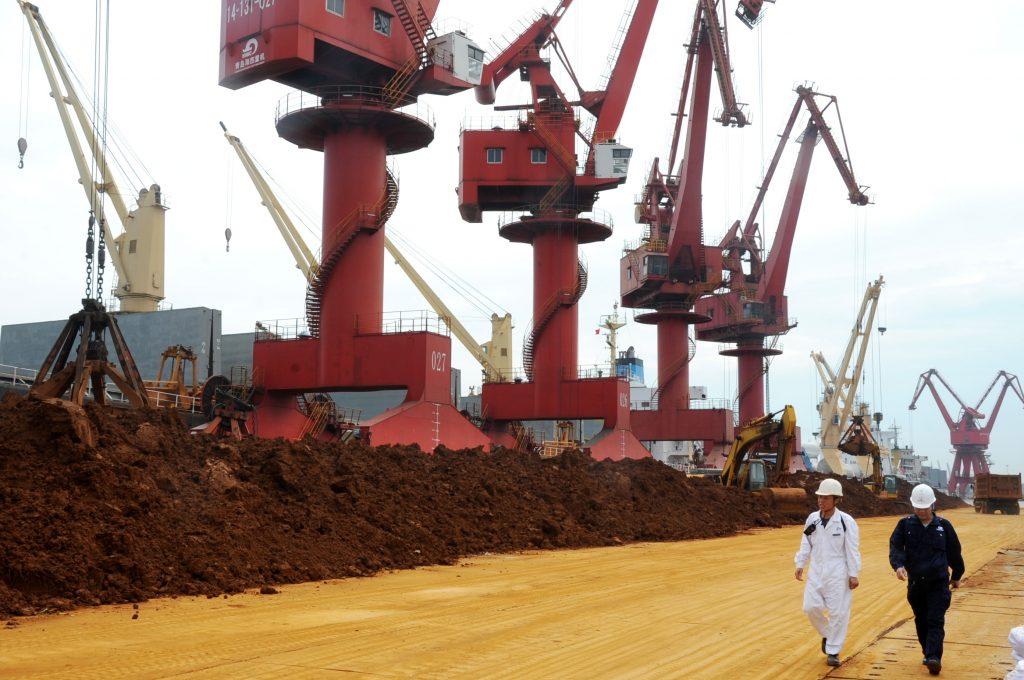 Des inspecteurs chinois marchent le long des monticules de terres rares sur le port de Lianyungang dans le Jiangsu, au nord de Shanghai sur la côte est chinoise, le 22 mai 2016. (Crédits : Wang chun / Imaginechina / via AFP)