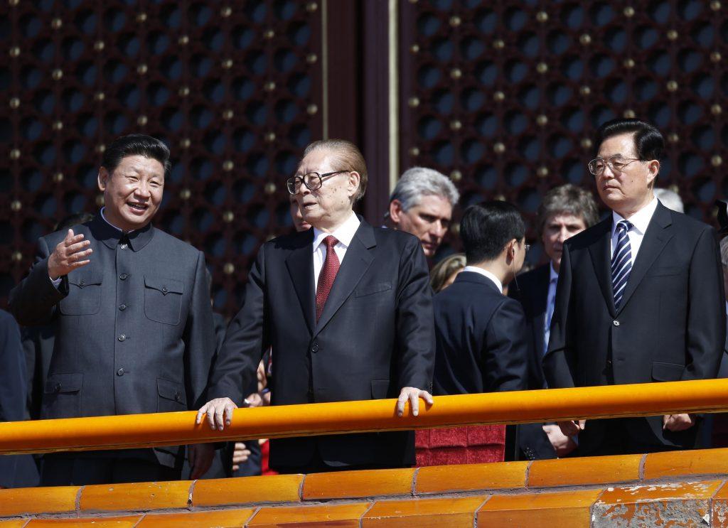 Le président chinois Xi Jinping parle avec l'ancien président Jiang Zemin, aux côtés de celui qui lui succéda, Hu Jintao, sur la place Tian'anmen à Pékin, le 3 septembre 2015, lors du défilé militaire marquant le 70ème anniversaire de la victoire sur le Japon. (Crédits : AFP PHOTO)