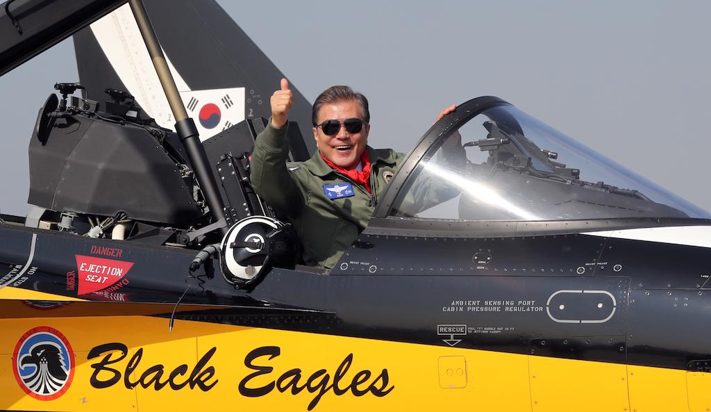 Le président sud-coréen Moon Jae-In dans un avion T-50 de l'équipe sud-coréenne de vol acrobatique Black Eagles lors de la cérémonie d'ouverture du Salon international de l'aérospatial et de la défense de Séoul (ADEX) à la base militaire de Seongnam, au sud de la capitale sud-coréenne, le 17 octobre 2017. (Crédits : STR / YONHAP / AFP)
