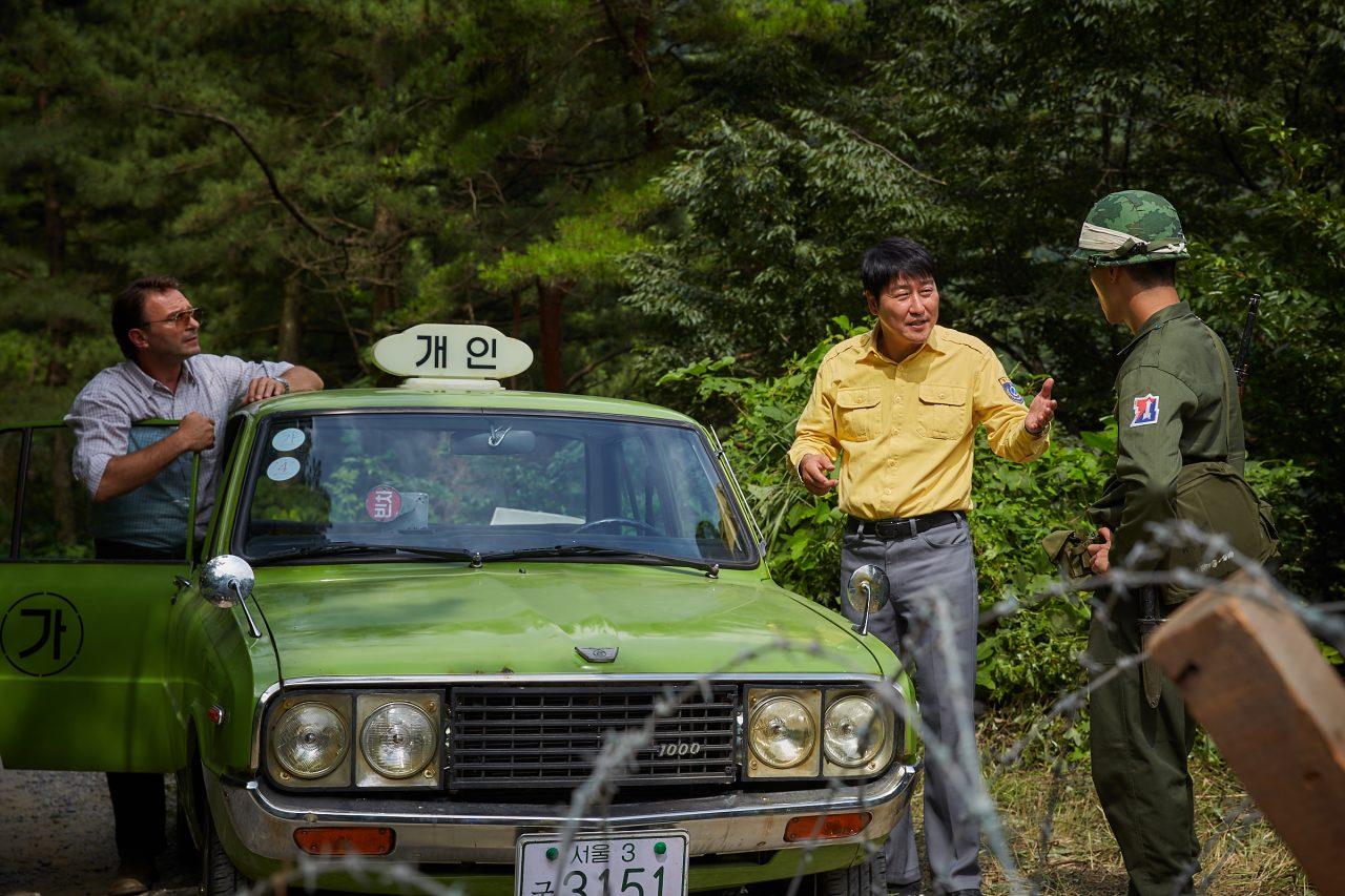 """Man-Seob et Hinzpeter tentent de passer le blocus imposé par l'armée. Extrait du film """"A Taxi Driver"""" de Jang Hoon. (Crédits : DR)"""