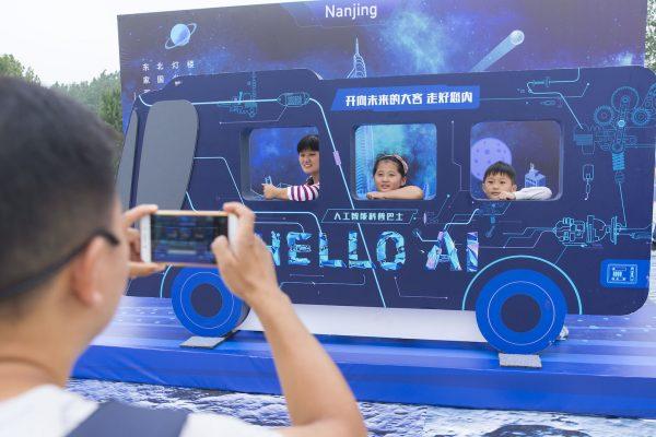 """""""Hello AI !"""", """"Salut l'intelligence artificielle !"""" Des visiteurs chinois expérimentent l'intelligence artificielle dans le Baidu AI Bus lors d'une exposition de vulgarisation scientifique organisée par le géant chinois des moteurs de recherche à Nankin, dans la province chinoise du Jiangsu, le 8 septembre 2017. (Crédits : CHENG JIABEI / IMAGINECHINA / via AFP)"""