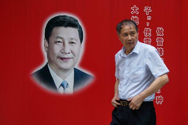 Un habitant de Shanghai passe devant une photo du président chinois Xi Jinping le 28 septembre 2017. (Crédits : AFP PHOTO / CHANDAN KHANNA)
