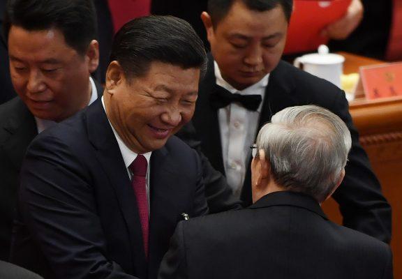 """Le président chinois Xi Jinping salue l'ancien Premier ministre Zhu Rongji lors de la clôture du 19ème Congrès du Parti communiste chinois dans le Grand Hall du Peuple à Pékin, le 24 octobre 2017. Le secrétaire général du Parti a obtenu sans surprise un nouveau mandat de 5 ans et l'inscription de sa """"pensée"""" avec son nom dans la Charte du Parti, faisant de lui l'égal de Mao et deng au panthéon communiste chinois. (Crédits : AFP PHOTO / GREG BAKER)"""