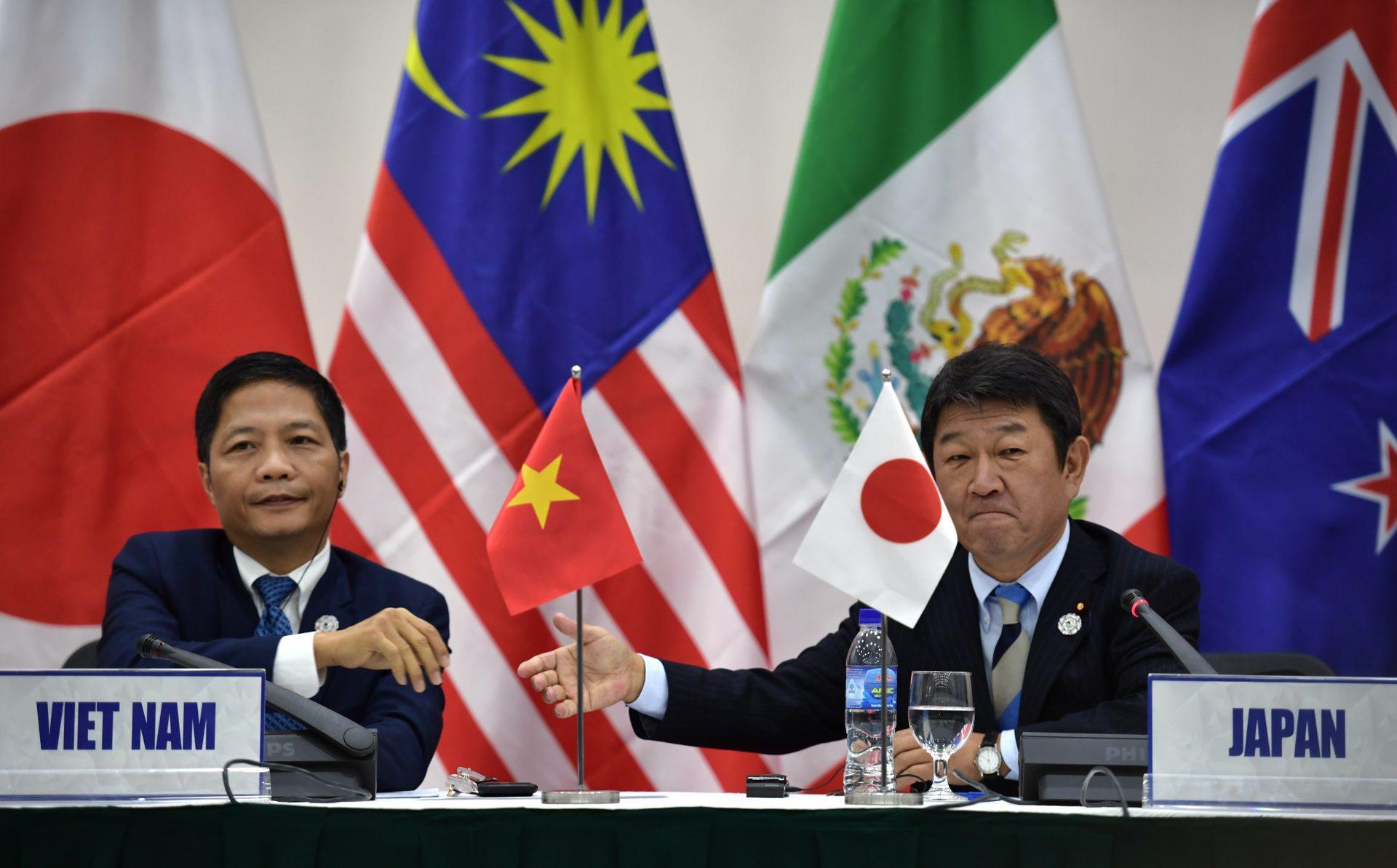 Le ministre vietnamien du Commerce Tran Tuan Anh (à gauche) s'apprête à serrer la main du ministre japonais de la Revitalisaiotn économique Toshimitsu Motegi lors d'une conférence de presse sur le Transpacific Partnership (TPP) en marge du sommet de l'APEC ( Coopération économique de l'Asie-Pacifique) à Danang au Vietnam, le 11 novembre 2017. (Crédits : AFP PHOTO / Anthony WALLACE)
