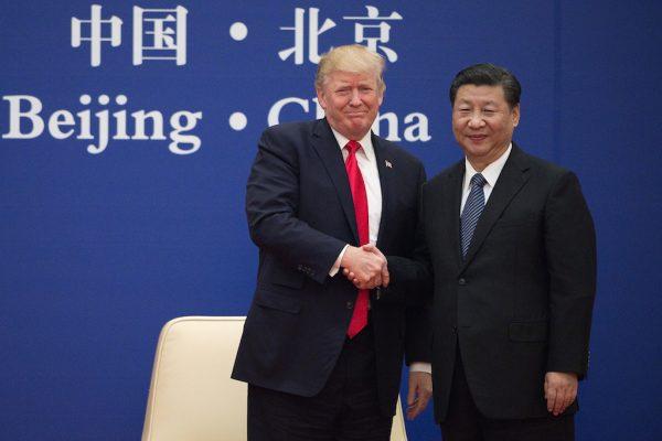 Le président américain Donald Trump se force à sourire en serrant la main de son homologue chinois Xi Jinping lors de la signature de gros contrats au Grand Hall du Peuple à Pékin le 9 novembre 2017. (Crédits : AFP PHOTO / Nicolas ASFOURI)