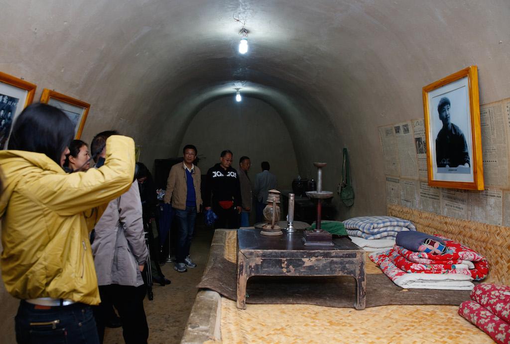 """Touristes venus visiter la grotte troglodyte à Liangjiahe (province du Shaanxi) dans laquelle l'actuel président chinois Xi Jinping a vécu lorsqu'il fut l'un des milliers de """"jeunes instruits"""" envoyés à la campagne par Mao. (Crédits : AFP PHOTO / STR / via AFP)"""