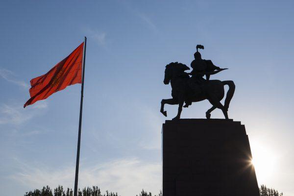 Le drapeau du Kirghizistan flotte devant la statue de Manas, place Ala-Too, à Bichkek. (Crédit : ESCUDERO PATRICK / HEMIS.FR / HEMIS, via AFP)