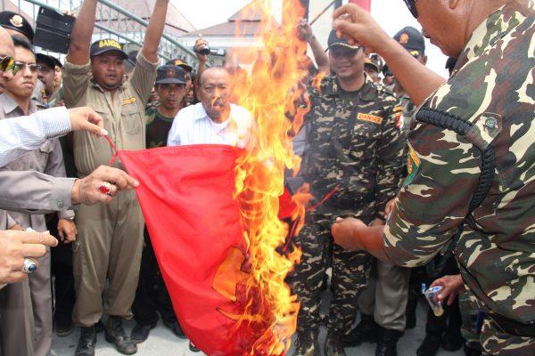 """Le 30 septembre 2015, des membres de l'organisation """"Nahdlatul Ulama"""" brûlent un drapeau communiste en marge d'une manifestation à la mémoire du dictateur Suharto."""