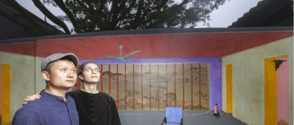 Le couple d'artiste franco-chinois Hu Jiamin et Marine Brossart portés disparus en Chine. Derrière eux, l'objet du litige avec la police : la fresque évoquant la chaise vide du Prix Nobel de la Paix Liu Xiaobo, peinte pour la biennale d'architecture à Shenzhen. (Source : South China Morning Post)
