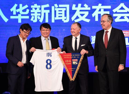 C'était il y a un plus d'un an : le président de l'Olympique Lyonnais Jean-Michel Aulas (deuxième à droite) et à ses côtés, le fondateur d'IDG Capital Partners Xiong Xiaoge lors de la cérémonie marquant l'entrée du fonds d'investissement chinois dans le capital du club de football français à hauteur de 20%, à Pékin le 13 décembre 2016. (Crédits : AFP PHOTO / Greg Baker)