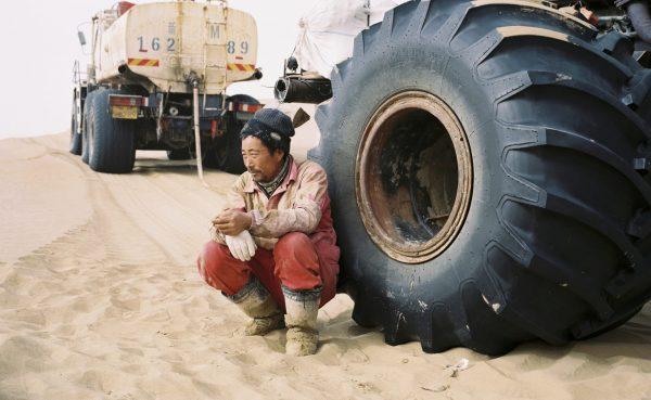 Décembre 2016. Un technicien qualifié de la compagnie pétrolière étatique chinoise CNPC, adossé à son véhicule après le déjeuner, dans le désert du Taklamakan dans la province chinoise du Xinjiang. (Copyright : Patrick Wack)