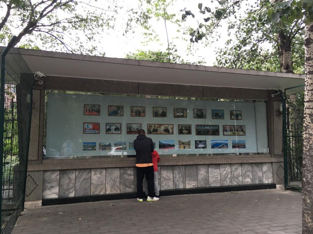 Un passant et son fils regardent les photos affichées à l'entrée de l'ambassade de Corée du Nord à Pékin : les principaux clichés du sommet intercoréen de Pyongyang entre Moon Jae-in et Kim Jong-un du 18 au 20 septembre 2018. (Crédits : Asialyst/Stéphane Lagarde)