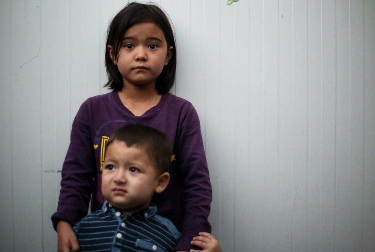 """Deux demandeurs d'asile afghans, une sœur et un frère âgés de 8 et 3 ans, résidents du camp de Moria sur l'île grecque de Lesbos, le 23 septembre 2018. Le garçon a des problèmes psychologiques, explique sa mère : """"Moria l'a rendu fou."""" (Copyright : Sarah Samya Anfis)"""