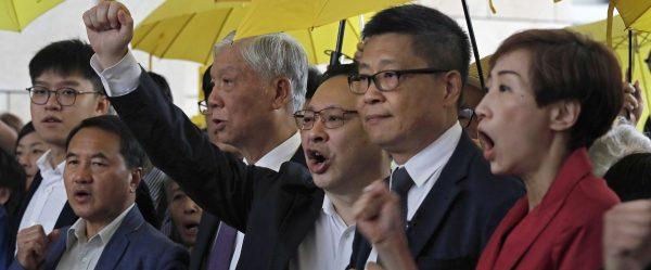 """Professeur de droit à la Hong Kong University, Benny Tai Yiu-ting (levant le poing au centre) est jugé depuis le 19 novembre 2018 pour son rôle dans le """"Mouvement des parapluies"""", avec huit autres organisateurs de cette manifestation massive, qui a bloqué les rues de la ville trois mois durant fin 2014 pour demander la démocratie et des élections libres. (Source : Fox 19)"""