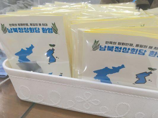 Distribution de cartes et pin's de la paix montrant une péninsule bleue sur fond blanc à Pusan en Corée du Sud fin novembre 2018. (Crédits : Asialyst / Stéphane Lagarde)