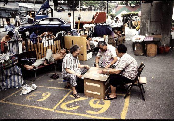 """Réunion de """"cages-men"""", des hommes sans famille et âgés, trop pauvres pour pouvoir habiter un appartement et qui vivent dans des cages grillagées de la taille d'une paillasse. Ils se retrouvent quotidiennement dans le parc du temple Tin Hau à Kowloon (Hong Kong) pour suivre les parties d'échecs dits """"des éléphants"""" (""""Jyutping"""" en cantonnais, """"Xiangqi"""" en mandarin, """"Shôji"""" en japonais). (Copyright : Bruno Birolli)"""