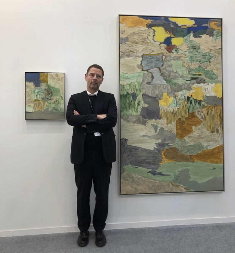 Burkhardt Riemschneider, directeur de la galerie berlinoise Neugerriemschneider, devant des toiles d'Andreas Eriksson, à l'India Art Fair à New Delhi le 30 janvier 2019. (Crédit : Michel Testard)