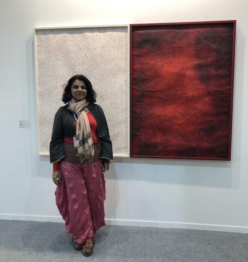 La peintre et photographe indienne M.G. Baswani devant l'une de ses toiles, à l'India Art Fair de New Delhi, le 30 janvier 2019. (Crédit : Michel Testard)