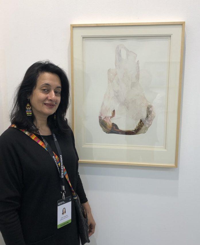 Tunty Chauhan, fondatrice et directrice de la Threshold Gallery New Delhi, devant une aquarelle de V. Ramesh, à l'India Art Fair à New Delhi, le 1er février 2019. (Crédit : Michel Testard)