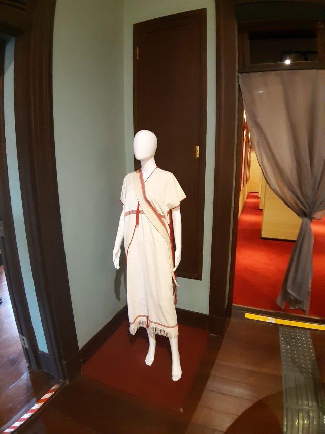 """Espace de l'exposition """"Decoding Thainess"""" au Palais du Siam à Bangkok. Le costume de l'ethnie Karen exposé à part et pas dans la posiiton du """"wai"""", la salutation caractéristique des Thaïs. (Crédit : Suzanne Lamour)"""