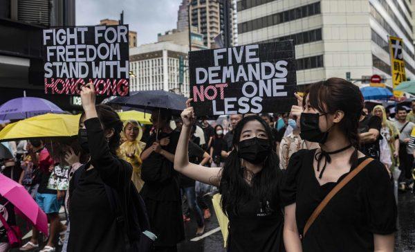 """""""Battez-vous pour la liberté, soutenez Hong Kong"""", """"cinq demandes, pas une de moins"""". La seconde pancarte fait référence aux revendications des manifestants hongkongais : 1. retirer complètement des discussions politiques la loi sur l'extradition ; 2. mettre en place le suffrage universel dans la démocratie de Hong-Kong ; 3. retirer les termes """"émeutes"""" et """"émeutiers"""" qualifiant les manifestations et les manifestants, instaurés par la cheffe du gouvernement, et par ce fait, libérer toute personne incarcérée en abandonnant toute poursuite judiciaire ; 4. créer une commission d'enquête externe et indépendante, pour rédiger des rapports sur les violences policières et mettre en lumière toutes les disparitions non expliquées et les attaques répétées des triades chinoises sur les manifestants isolés ; 5. la démission de la cheffe du gouvernement, Carrie Lam. (Copyright : Naomi Goddard)"""