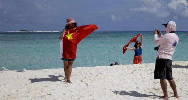 Des touristes chinois prennent une photo souvenir sur l'île de Quanfu (préfecture de Sansha) dans l'archipel disputé des Paracels, au sud de Hainan, en mer de Chine méridionale, le 14 septembre 2014. (Source : VOA NEWS)