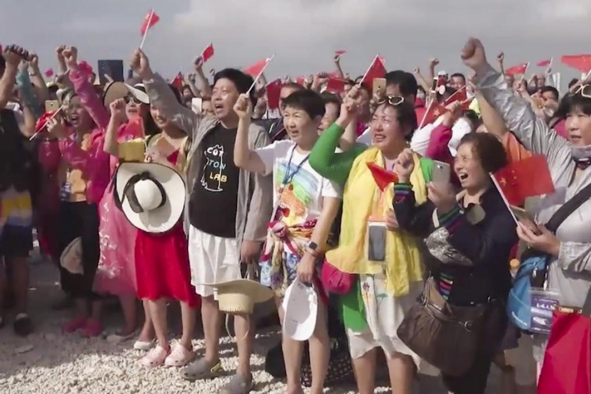 Des touristes chinois assistent à une cérémonie de lever de drapeau sur l'île de Yagong. (Source : SCMP)