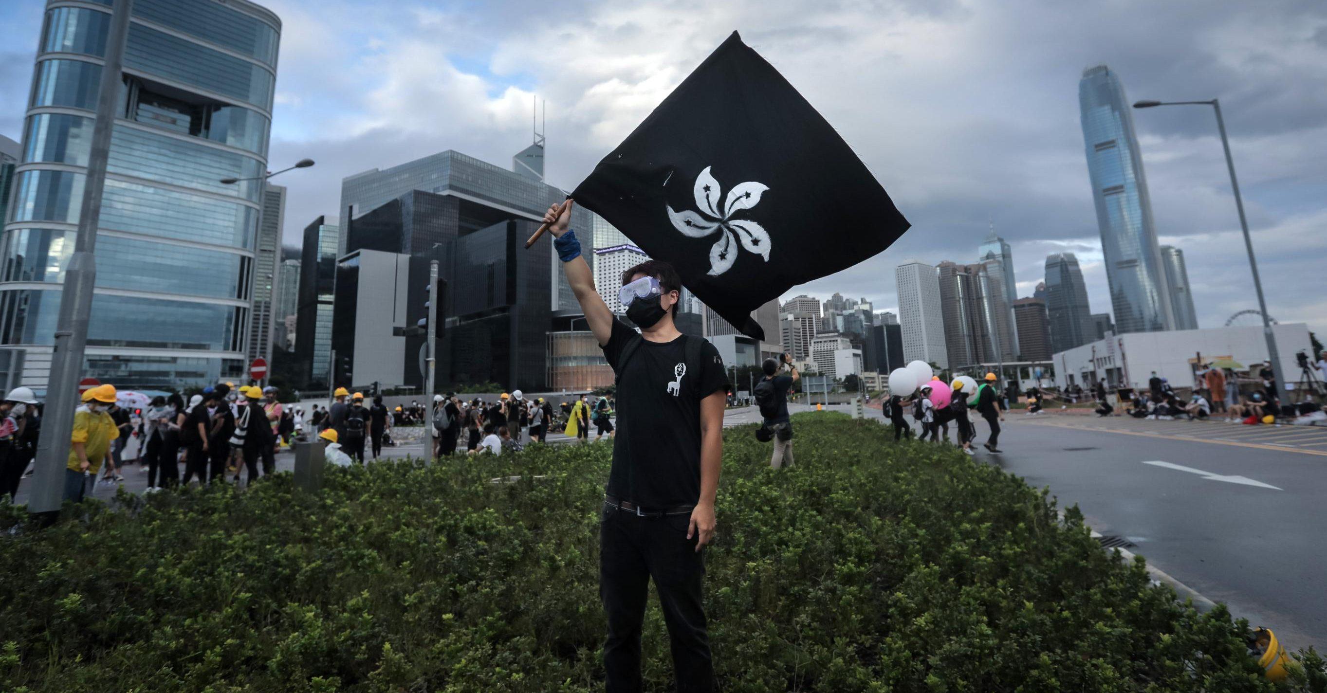 Un manifestant agitant le drapeau de Hong Kong sur fond noir. (Source : CNN)