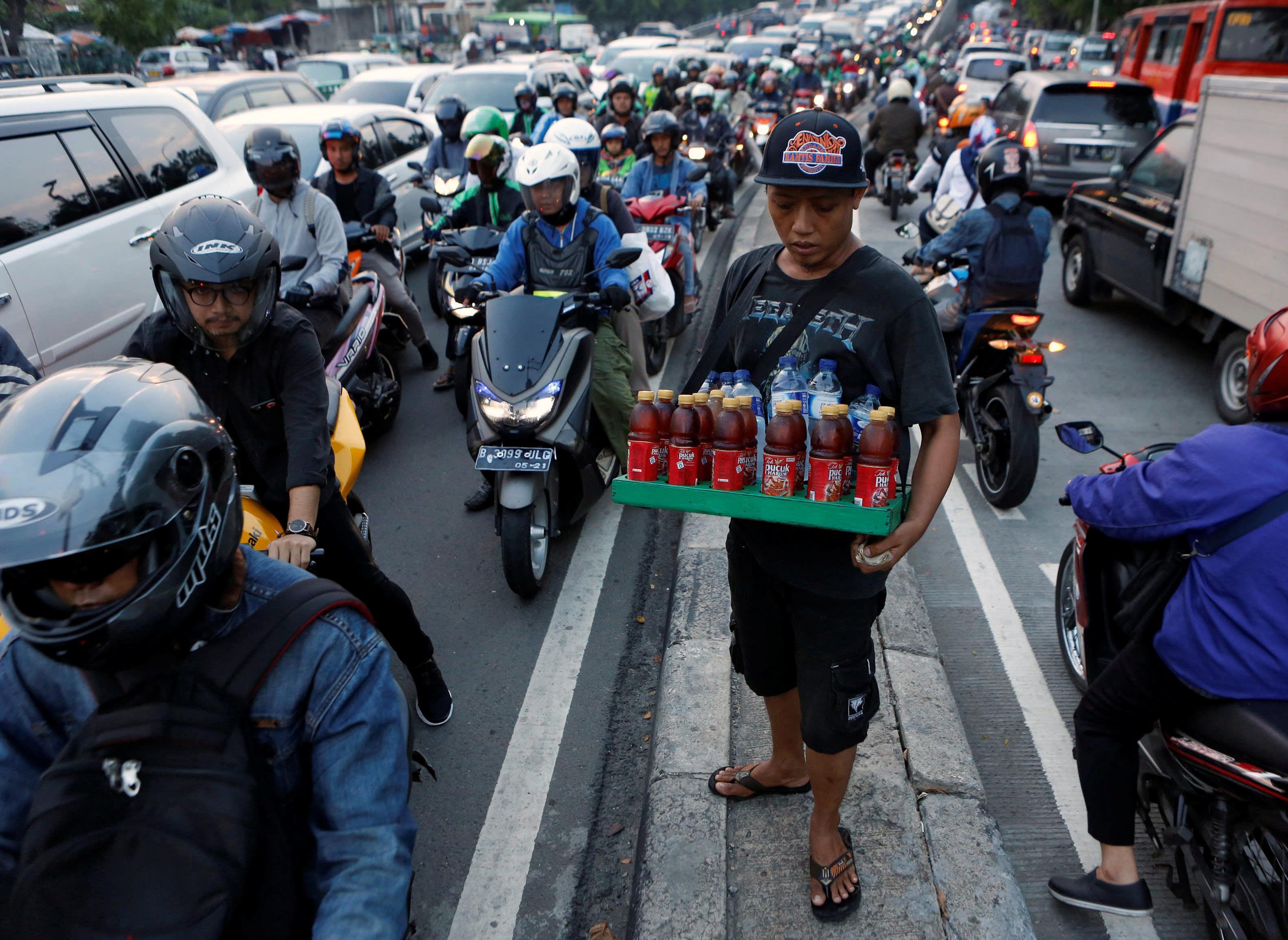 Un vendeur de rue au milieu des embouteillages à Jakarta. (Source : Nikkei Asian)