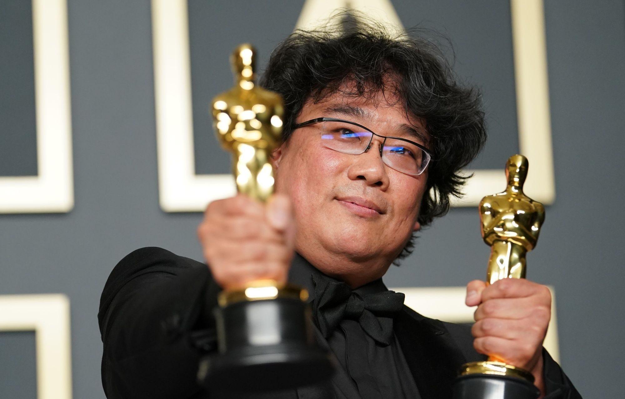"""Le réalisateur sud-coréen Bong Joon-ho brandit deux des quatre oscars de son film """"Parasite"""", récompensé dans les catégories meilleur film, meilleur film international, meilleur réalisateur et meilleur scénario original, à Los Angeles le 9 février 2020. (Source : Yahoo News)"""