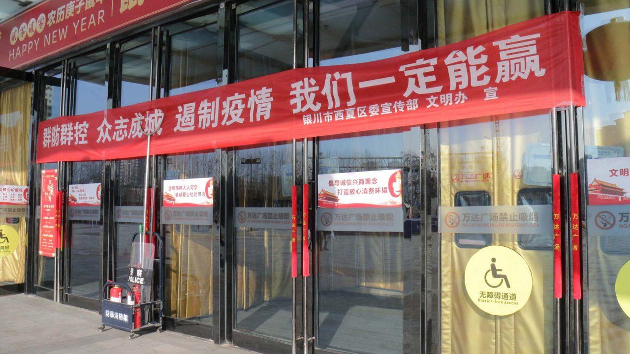 """""""Évitons les rassemblements de foule, la volonté de tous fait rempart, contenons l'épidémie et nous vaincrons à coup sûr"""", clame cette banderole accrochée sur la place déserte du Wanda Plaza, le plus grand centre commercial de Yinchuan. (Crédit : Thibaud Mougin / SOPA images)"""