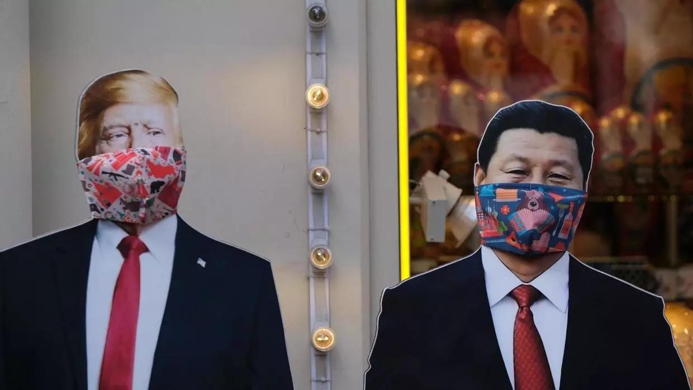 Deux effigies de Donald Trump et de Xi Jinping, masquées, dans une rue de Moscou en mars 2020. Crédit : REUTERS / Evgenia Novozhenina via RFI.