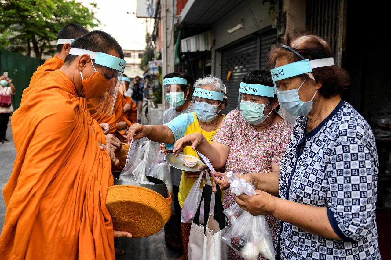 Des moines bouddhistes portant le masque pour se protéger du coronavirus récoltent l'aumône à Bangkok, le 31 mars 2020. (Source : Reuters)