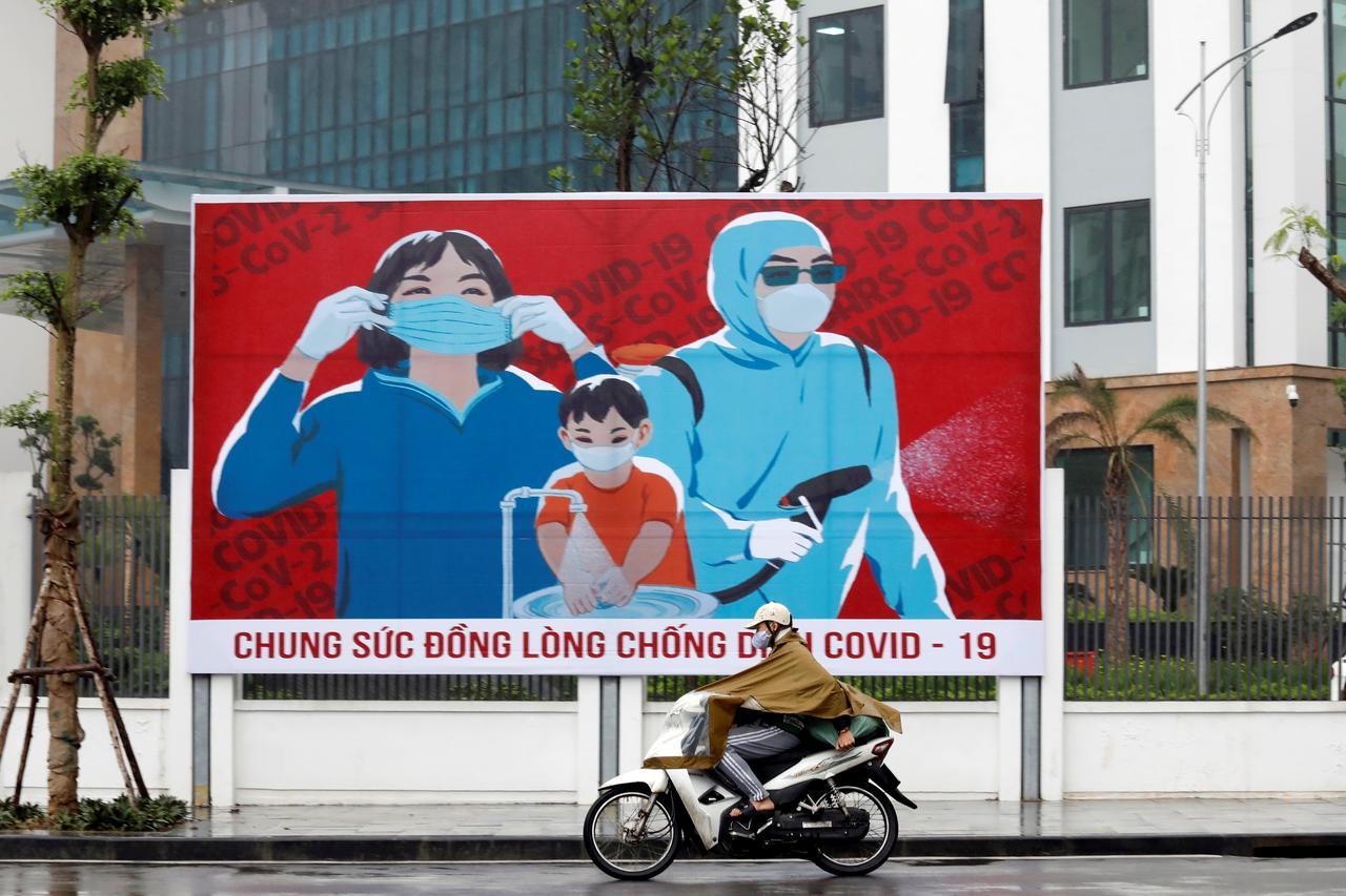 Un homme à scooter porte un masque tandis qu'il passe devant une affiche de propagande sur les mesures de précaution contre le coronavirus. Source : Reuters / Kham.