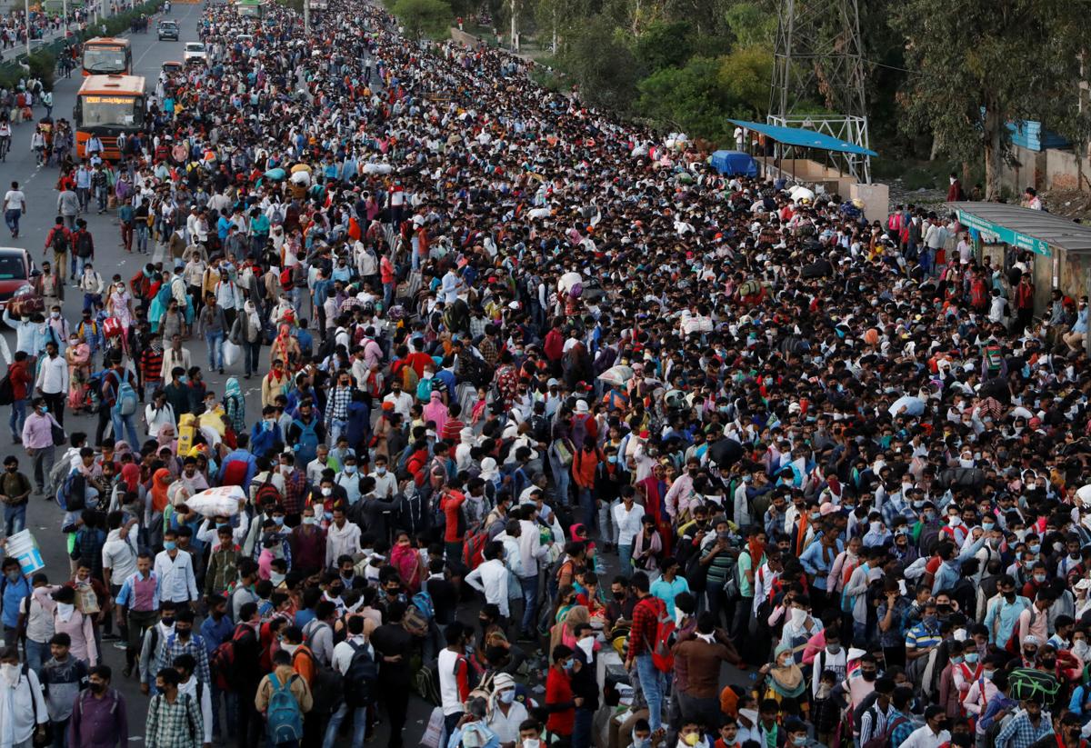Une foule de travailleurs migrants tentent d'embraquer dans un bus pour rejoindre leur village, le 28 mars 2020, à Ghaziabad, dans la banlieue de Delhi, après la décision d'instaurer un confinement total de l'Inde pendant 21 jours. (Source : Asie Nikkei Review)