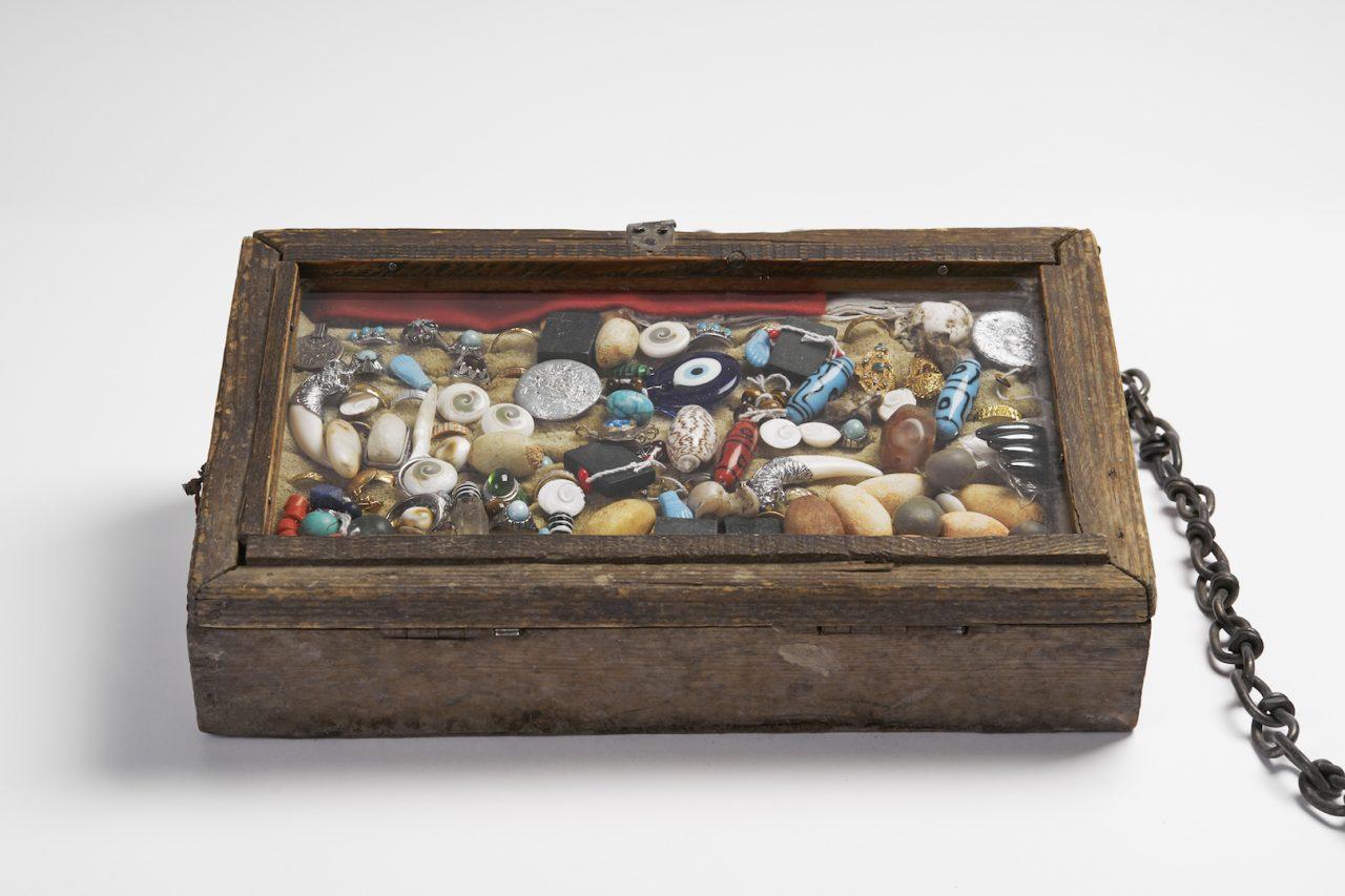 """Photographie d'une boîte contenant des pierres de kharmohra et autres talismans. Détail de l'installation d'Abdul Wahab Mohmand, """"Le siège de la mort"""", production 2019. Collection de l'artiste. (Copyright : David Giancatarina)"""