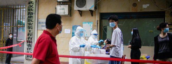 Des soignants chinois opèrent des tests d'amplification de l'acide nucléique à des résidents de Wuhan, capitale provinciale du Hubei et premier foyer officiel de la pandémie de coronavirus, le 15 mai 2020. (Source : Reuters)