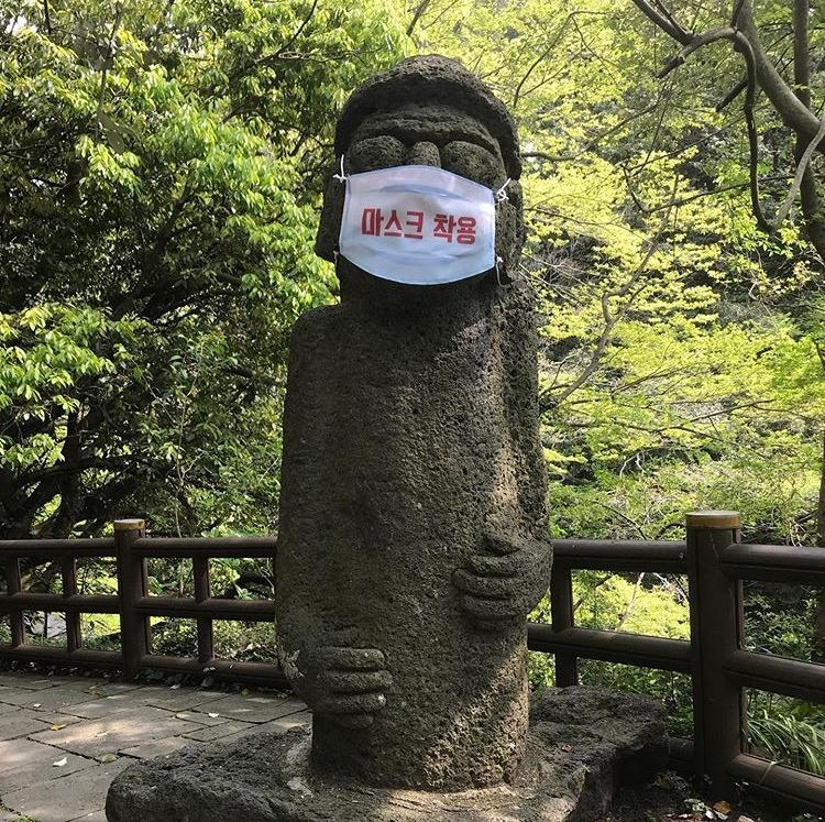 """Les """"Dol hareubangs"""" ou """"grands-pères de pierre"""", ces statues traditionnelles de l'île sud-coréenne de Jeju aujourd'hui masquées pour inciter les touristes à continuer de le porter, le 3 mai 2020. (Copyright : Park Tae-gun)"""