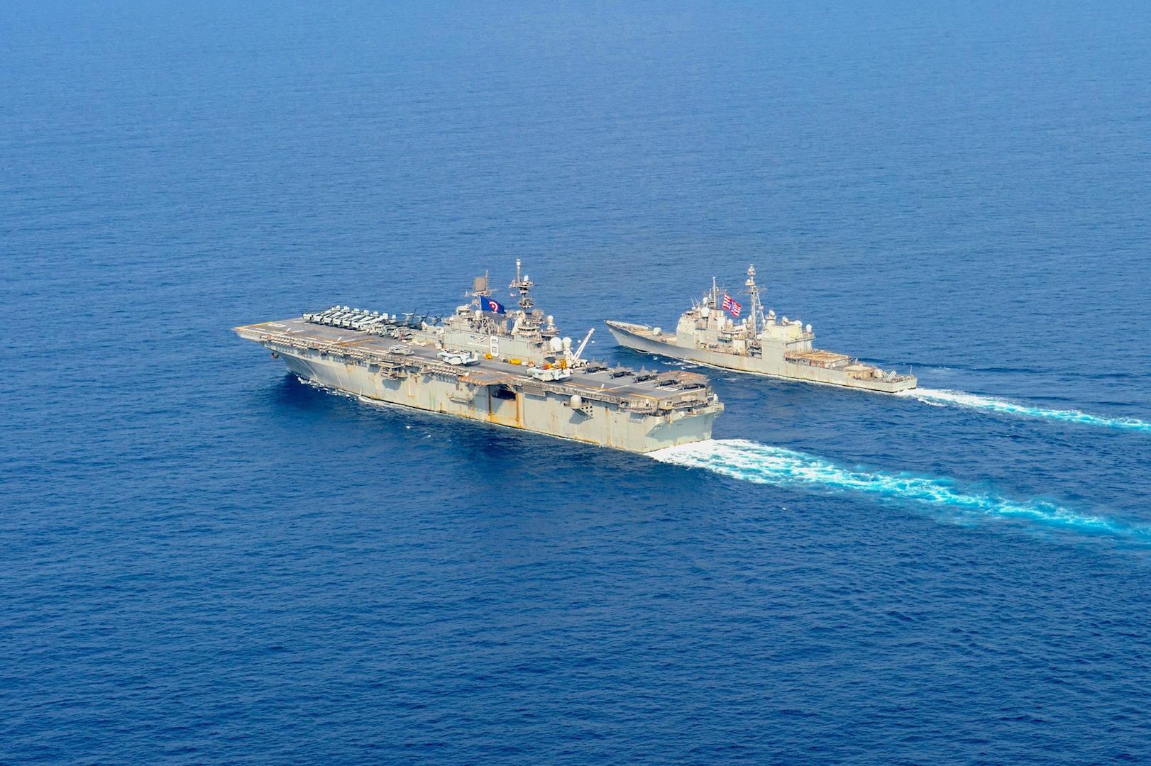 Le navire américain d'assaut amphibie USS America (LHA 6), à gauche, et le croiseur lance-missiles de classe Ticonderoga USS Bunker Hill (CG 52) traversent la mer de Chine du Sud. (Source : USNI)