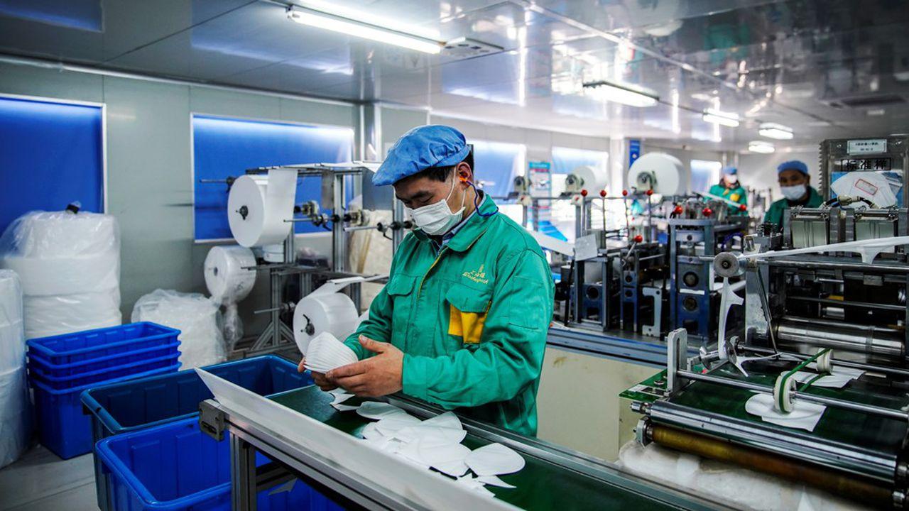 Des ouvriers chinois dans une usine de fabrication de masques à Shanghai, le 31 janvier 2020. (Source : Echos)