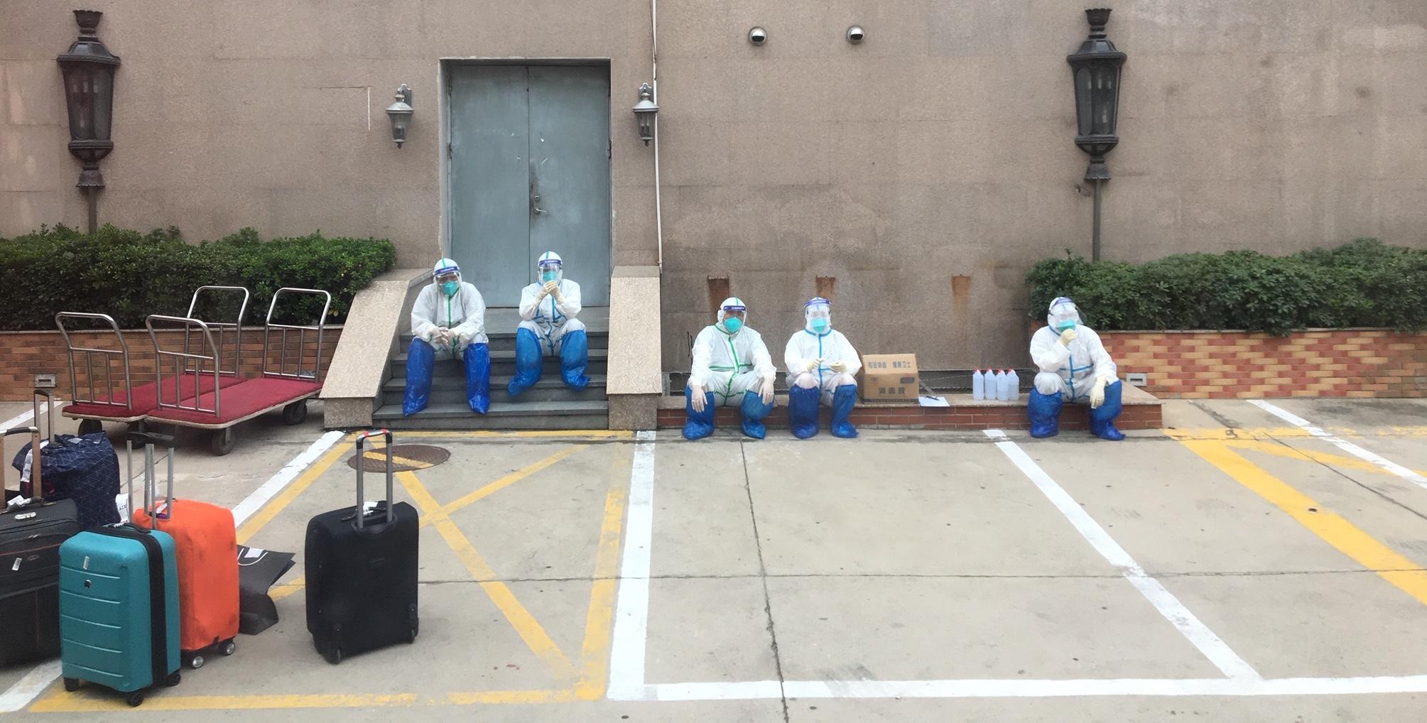 Les hommes en combinaisons sur le parking de l'hôtel à Pékin. (Copyright : Stéphane Lagarde)