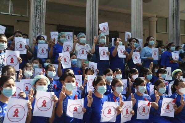 """Le 5 février 2021 à Rangoun, des professeurs de la Yangon Education University arborent des pancartes avec le slogan """"Les professeurs de Birmanie en désobéissance civile"""", après le coup d'État militaire du 1er février. Ils font le salut à trois doigts, le signe des militants pro-démocratie en Thaïlande, inspiré de la trilogie """"Hunger Games"""". (Source : APNEWS)"""