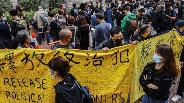 """""""Libérez les prisonniers politiques"""" appelle la banderole lors du rassemblement en soutien des 47 militants pro-démocratie inculpés pour """"subversion"""", devant le tribunal de Kowloon West, le 1er mars 2021. (Source : QZ)"""