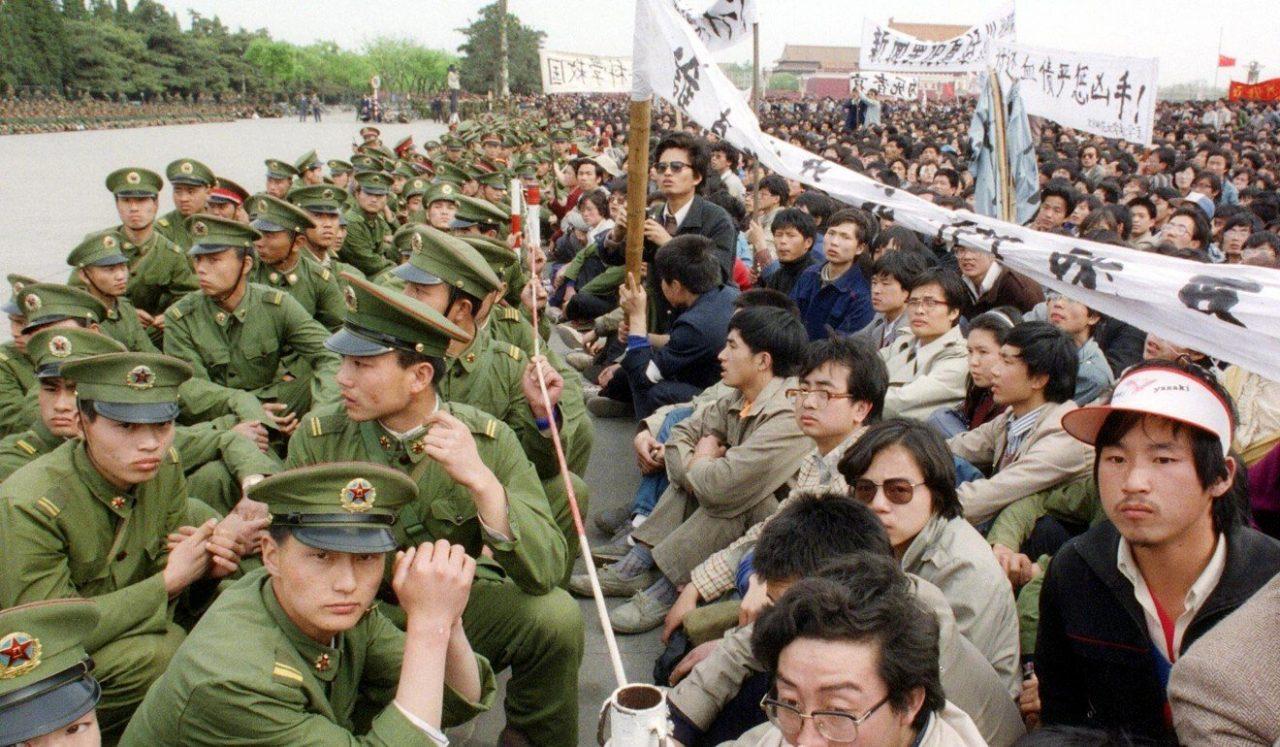 Le 22 avril 1989, manifestants étudiants assis face à face avec la police devant le Grand Hall du Peuple à Pékin après la mort de Hu Yaobang. (Source : SCMP)