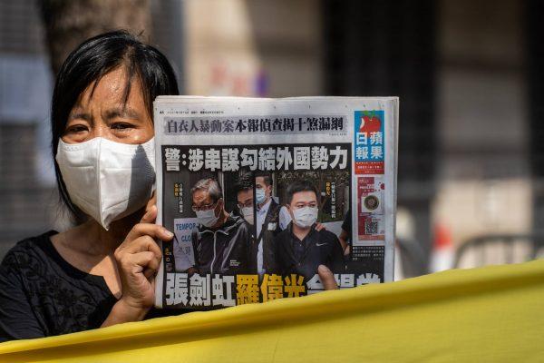 """Une Hongkongaise tient la Une du quotidien """"Apple Daily"""" avant la comparution de son directeur général Cheung Kim-hung et de son rédacteur en chef Ryan Law devant le Tribunal de West Kowloon à Hong Kong, le 19 juin 2021. (Source : Japan Times)"""